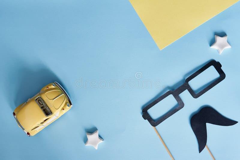 Szczęśliwy ojca dnia odgórny widok Dekoracyjny czerń papieru wąsy, szkła i koloru żółtego zabawkarski samochód na błękitnym tle z obraz royalty free