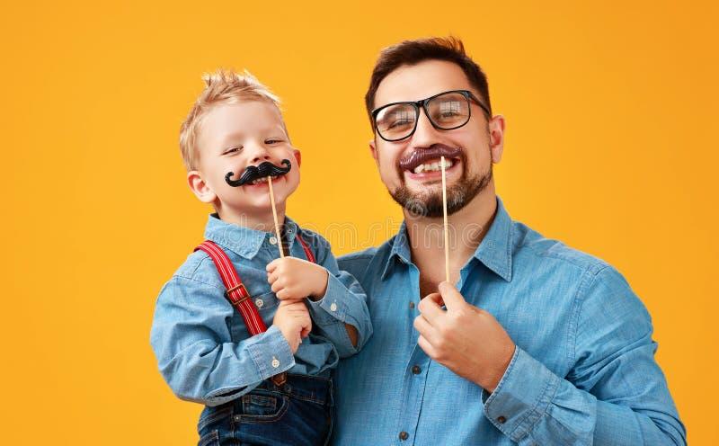 Szczęśliwy ojca dzień! śmieszny tata i syn z wąsy błaź się wokoło na żółtym tle zdjęcie royalty free