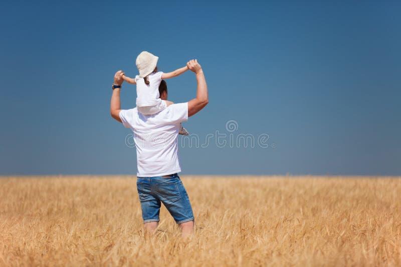 Szcz??liwy ojca i c?rki spacer w lata polu Natury pi?kno, niebieskie niebo i pole z z?ot? banatk?, styl ?ycia plenerowy obraz stock