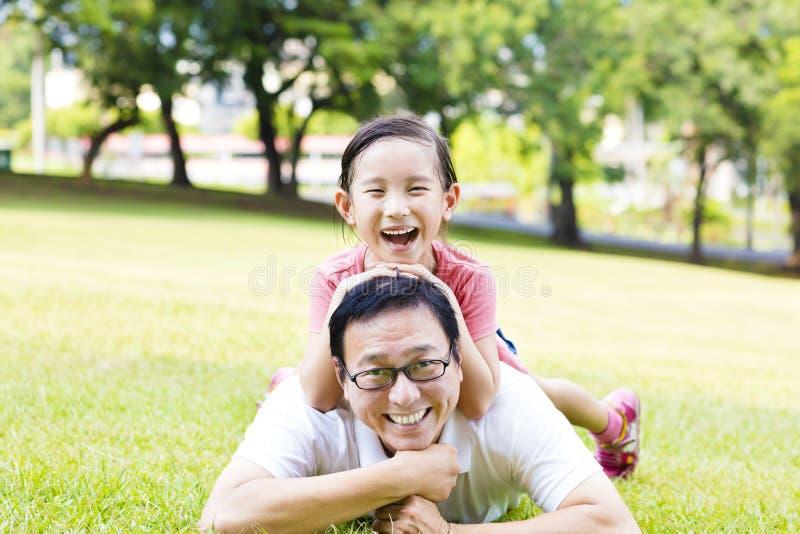 Szczęśliwy ojca i małej dziewczynki lying on the beach na trawie obrazy stock