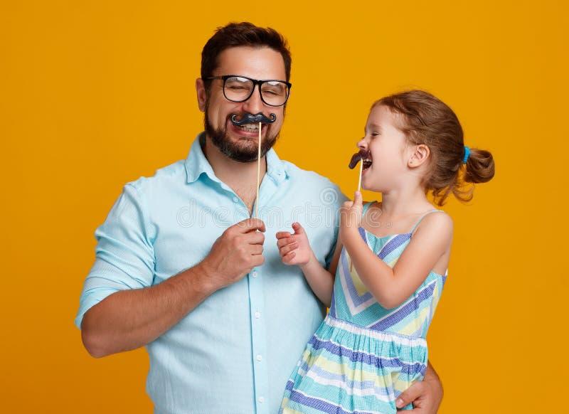 Szczęśliwy ojca ` s dzień! śmieszny tata i córka z wąsy błaźnić się zdjęcia stock
