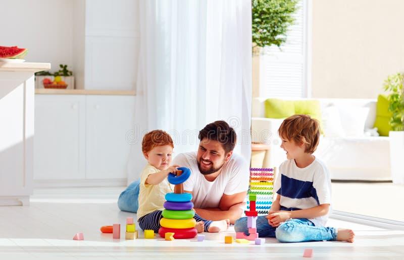 Szczęśliwy ojciec bawić się z synami w domu obraz stock