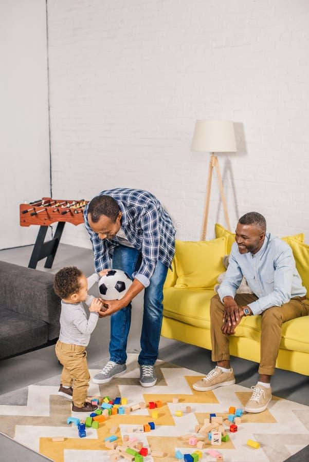 szczęśliwy ojciec i dziadek patrzeje uroczy berbeć pije od dziecko butelki podczas gdy bawić się z zabawkami zdjęcia stock