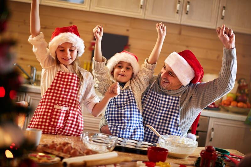 Szczęśliwy ojciec i dzieci robi Bożenarodzeniowym ciastkom obrazy stock