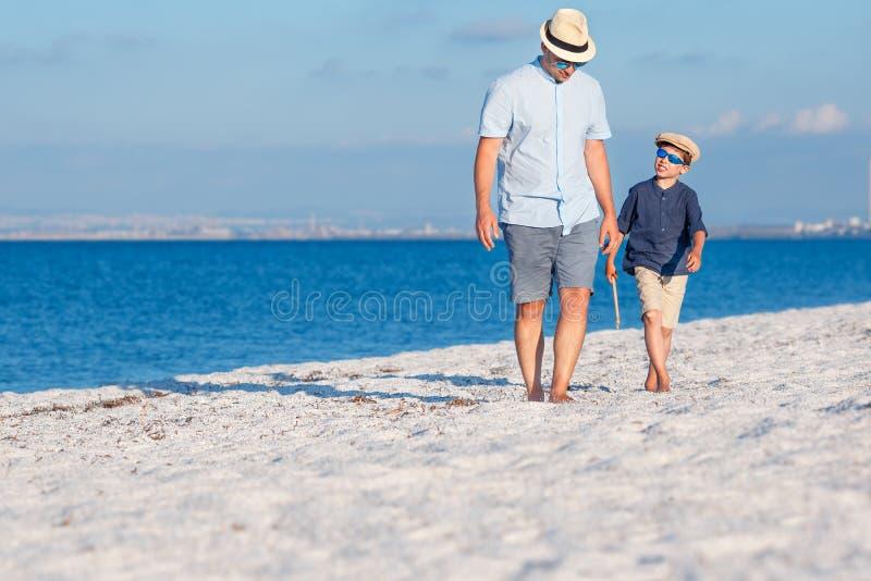 Szczęśliwy ojciec i jego syn ma zabawę przy plażą zdjęcie stock