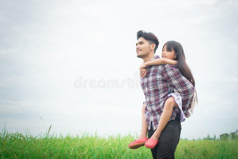 Szczęśliwy ojciec i mała dziewczynka bawić się przy łąkami odpowiadamy, cieszymy się, obrazy royalty free