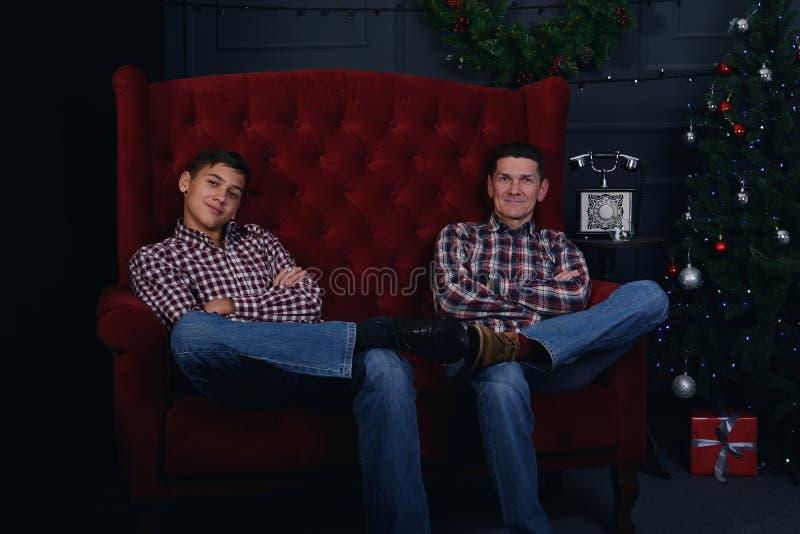 Szczęśliwy ojciec i nastoletni syn jesteśmy siedzieć skrzyżny w przodzie o zdjęcia stock