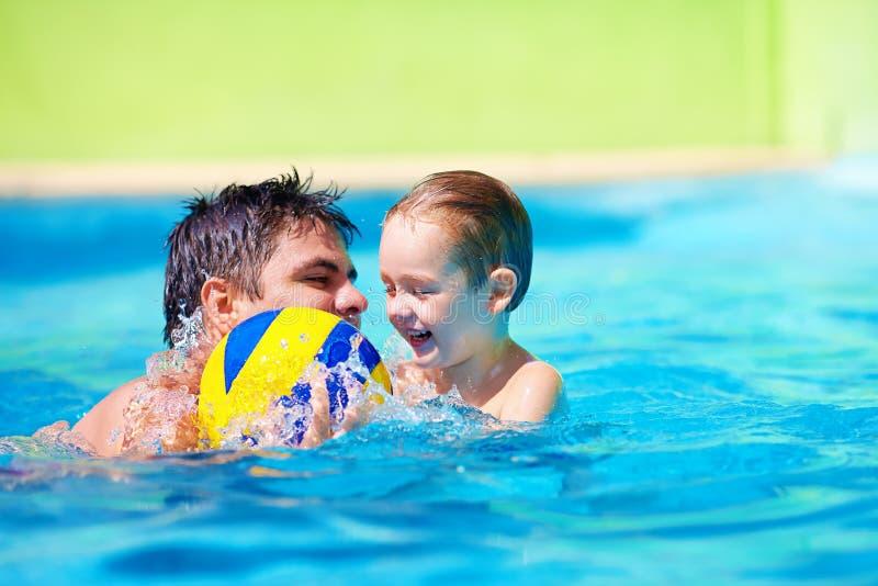 Szczęśliwy ojciec i syn bawić się z piłką w basenie fotografia royalty free
