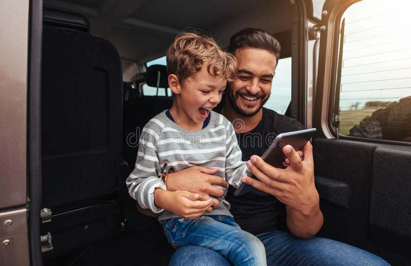 Szczęśliwy ojciec i syn na wycieczce samochodowej używać cyfrową pastylkę obrazy royalty free