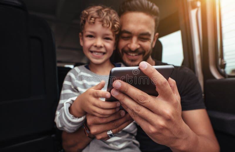 Szczęśliwy ojciec i syn przy plecy samochód z cyfrową pastylką obrazy royalty free