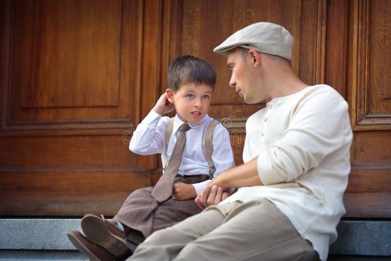 Szczęśliwy ojciec i syn relaksuje outdoors w mieście zdjęcia royalty free