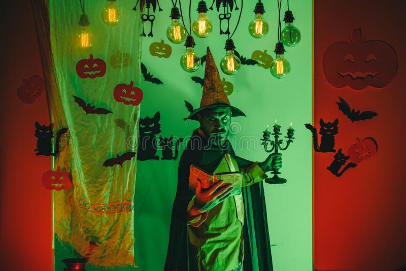 Szczęśliwy ojciec na Halloween tle z magik książką Mężczyzna wymawia czary, czyta magiczną książkę Mężczyzna horroru twarze obrazy stock