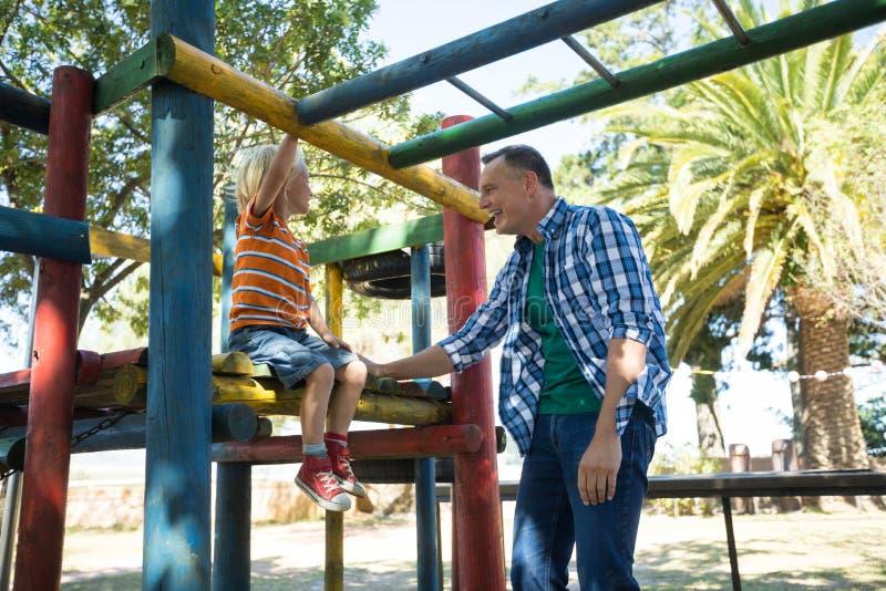 Szczęśliwy ojciec opowiada syna obsiadanie na dżungli gym obrazy royalty free