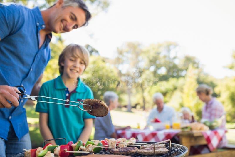 Szczęśliwy ojciec robi grillowi z jego synem obraz royalty free