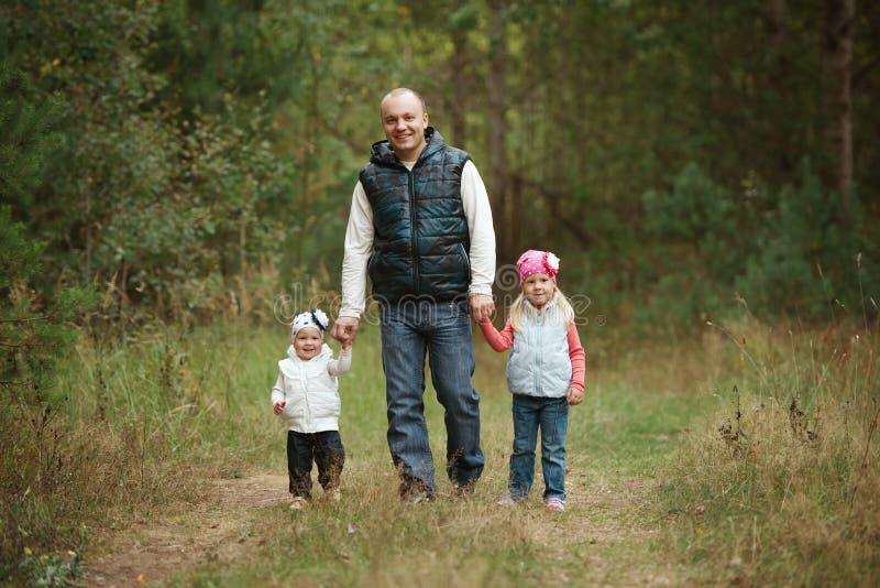 Szczęśliwy ojciec trzyma dwa małego daughers fotografia stock