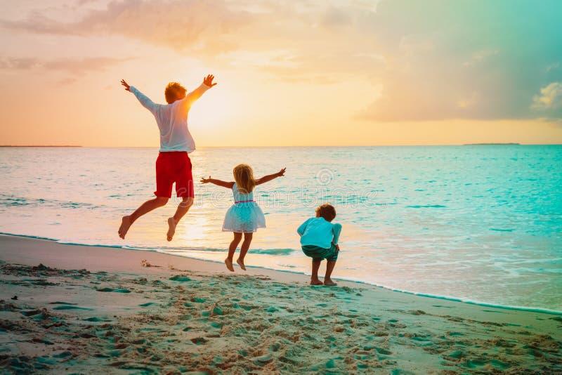 Szczęśliwy ojciec więdnie córki i syna sztukę na plaży obraz stock