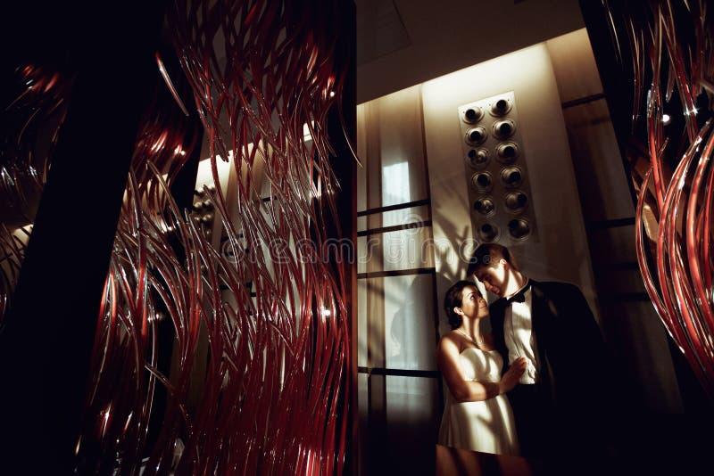 Szczęśliwy państwo młodzi stojak w cieniu hotelowych lamp obraz royalty free