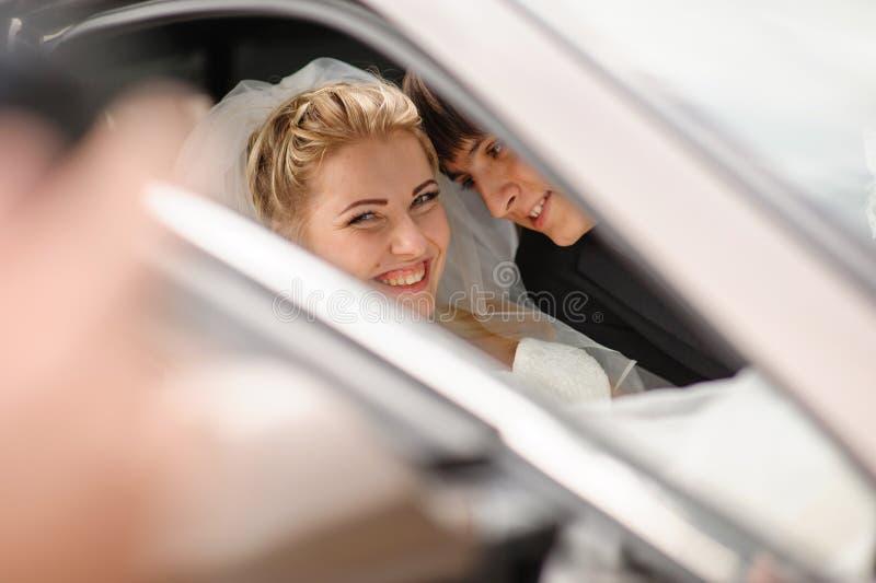 Szczęśliwy państwo młodzi w ślubnym samochodzie obrazy stock