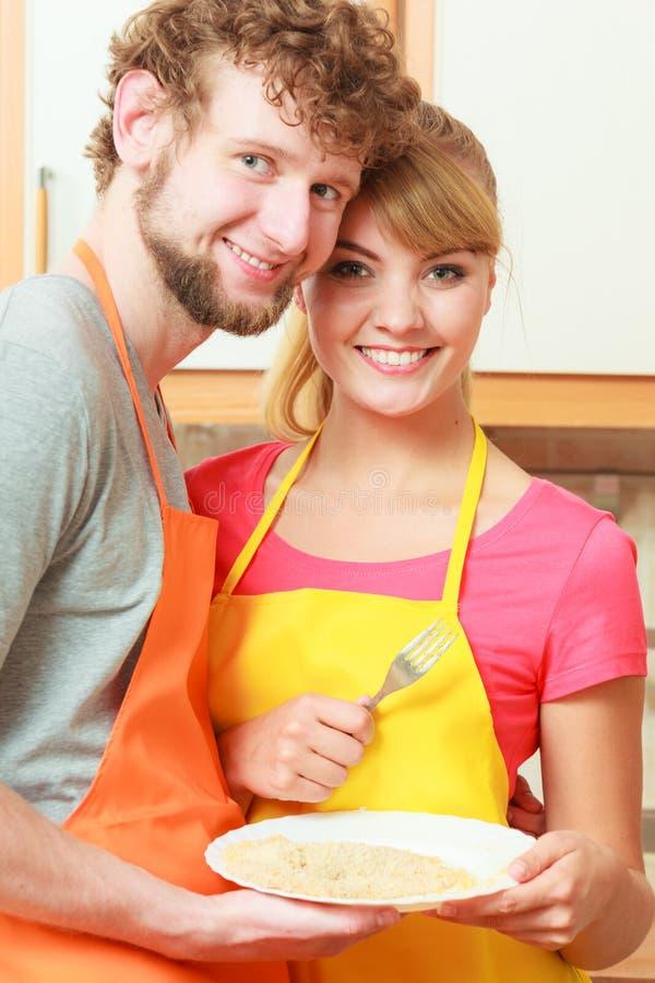 Szczęśliwy para mężczyzna i kobiety kucharstwo w kuchni zdjęcia royalty free