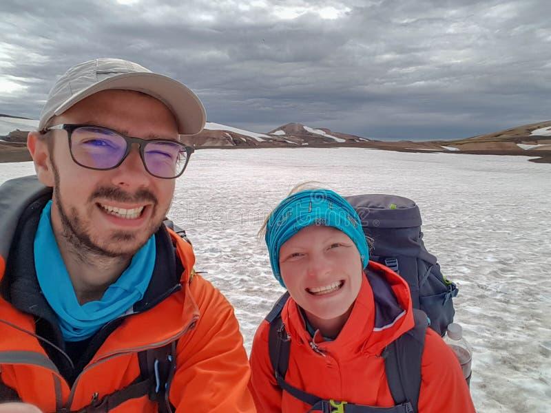 Szczęśliwy para mężczyzna, kobieta wycieczkuje wpólnie w górach z dużymi ciężkimi plecakami i Podróży przygody podróżomanii aktyw zdjęcia royalty free