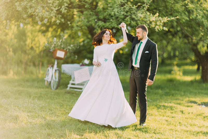 Szczęśliwy para małżeńska taniec na gazonie w zielonym pogodnym parku właśnie fotografia stock