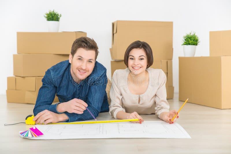 Szczęśliwy para rysunku plan ich mieszkanie zdjęcie stock
