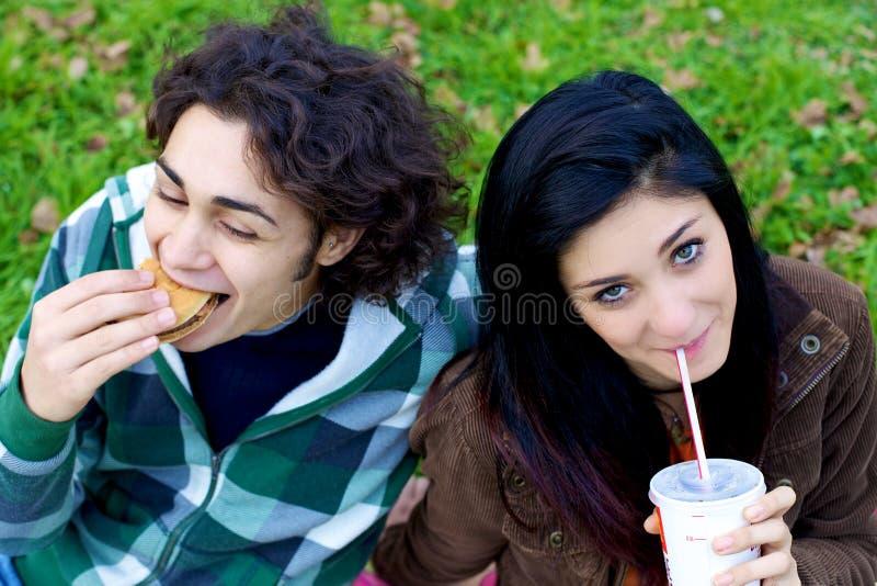 Szczęśliwy pary łasowania fasta food hamburger i soda w parku zdjęcie stock