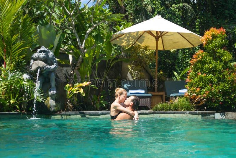 Szczęśliwy pary całowanie podczas gdy relaksujący w plenerowym zdrój nieskończoności basenie otaczającym z luksusowym tropikalnym fotografia stock