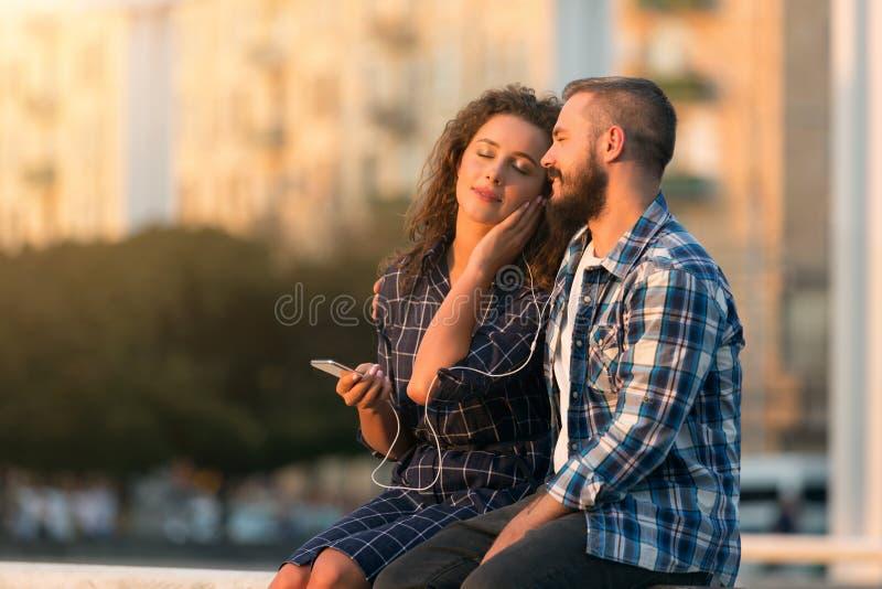 Szczęśliwy pary datowanie, cieszy się muzykę przy miasto zmierzchem fotografia royalty free
