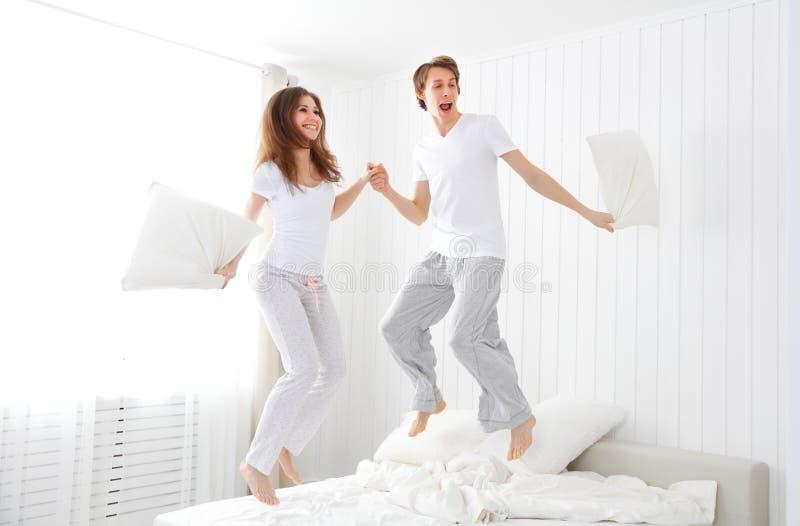 Szczęśliwy pary doskakiwanie i mieć zabawa w łóżku obraz stock