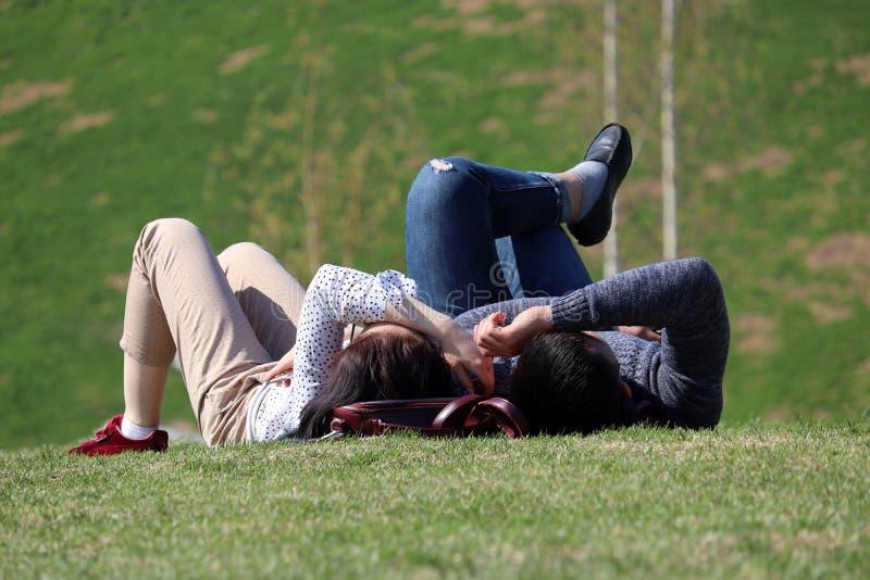 Szczęśliwy pary lying on the beach na zielonym wzgórzu na ciepłym słonecznym dniu, wiosna sezon obrazy stock