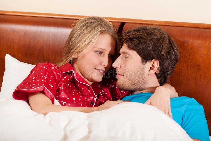 Szczęśliwy pary lying on the beach w łóżku fotografia stock