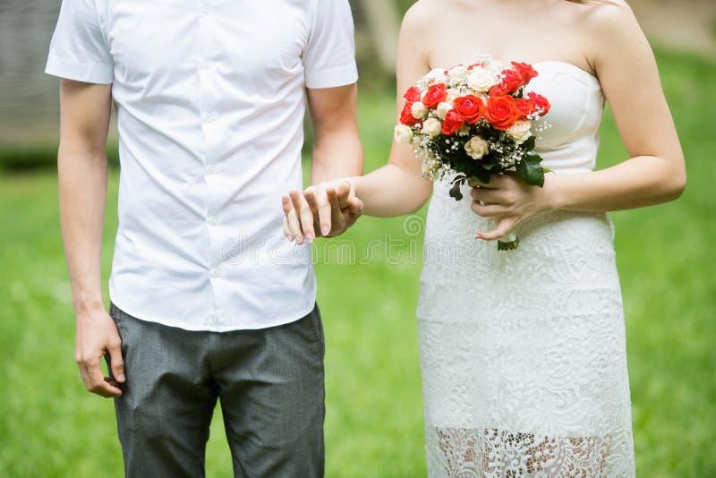 Szczęśliwy pary małżeńskiej mienie wręcza plenerowego z kwiatami zdjęcia royalty free