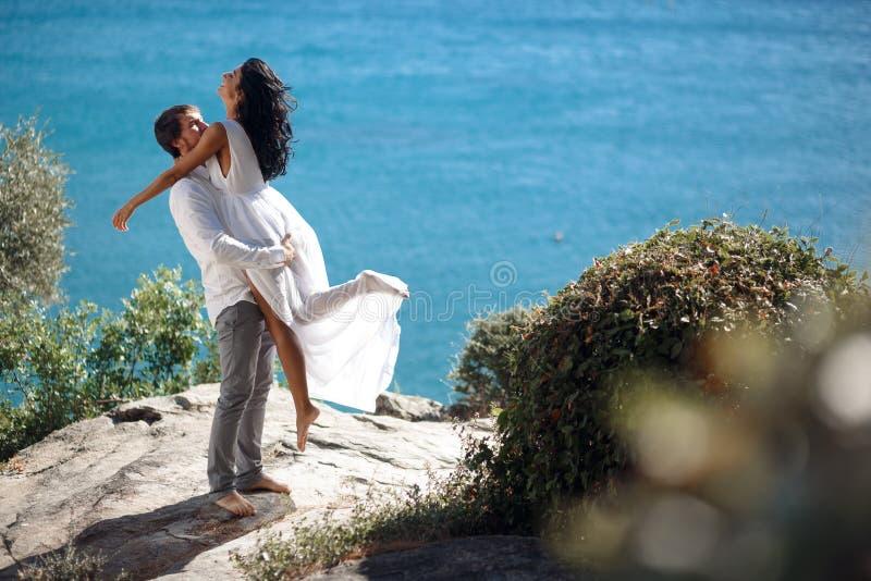 Szczęśliwy pary obejmowanie i całowanie, behinde piękny mediterrianean morze w Grecja seascape zdjęcie royalty free