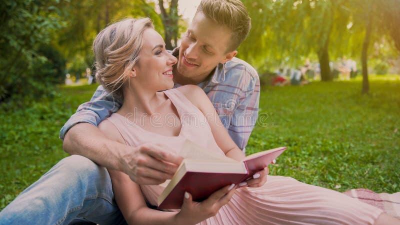 Szczęśliwy pary obsiadanie na dywanik czytelniczej książce i tenderly patrzeć each inny zdjęcia stock