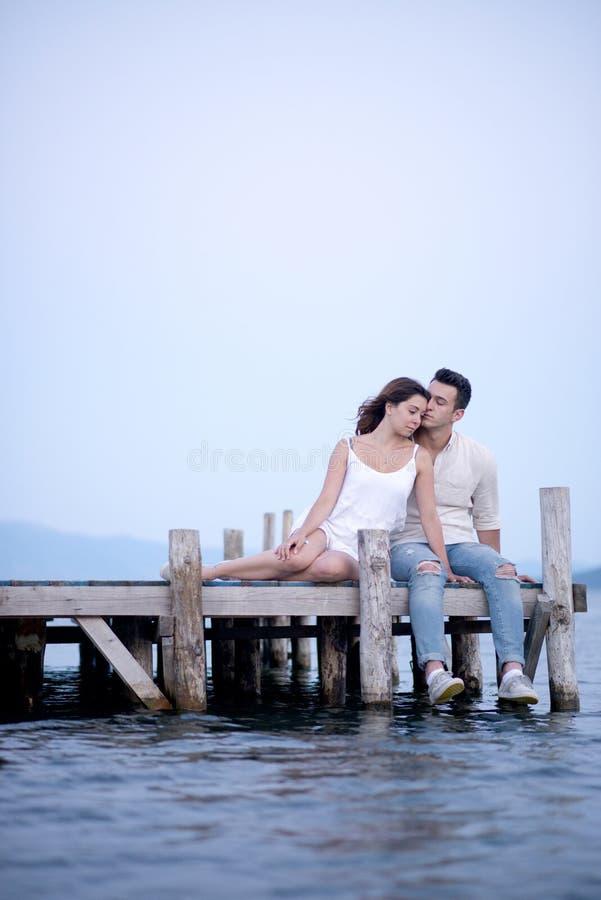 Szczęśliwy pary obsiadanie na molu na wakacje zdjęcie stock