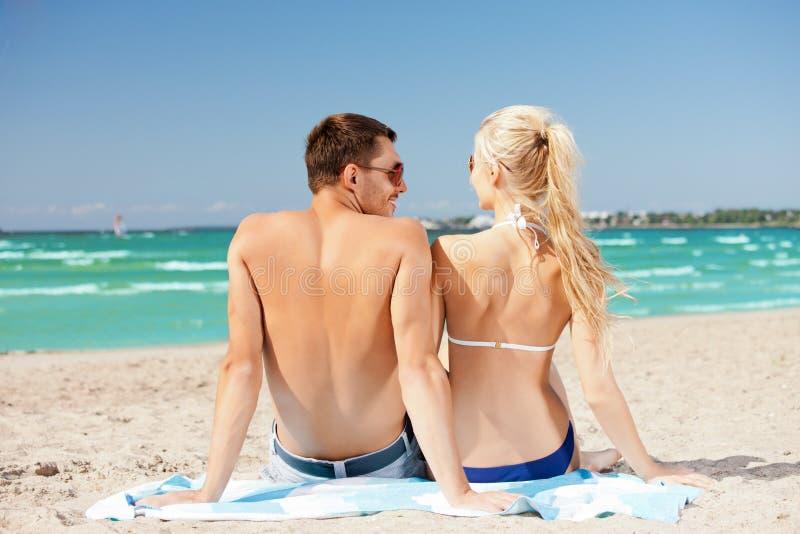 Szczęśliwy pary obsiadanie na plaży obraz stock