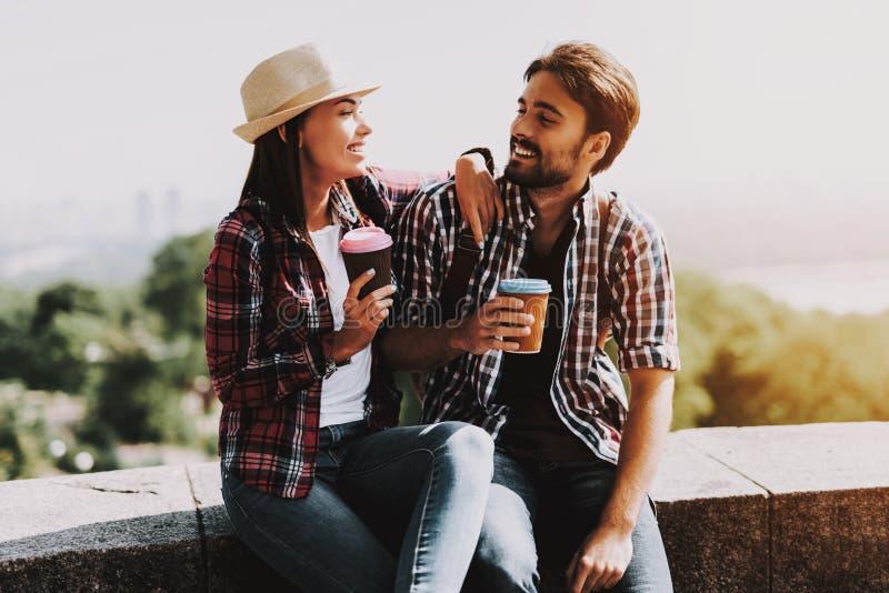 Szczęśliwy pary obsiadanie na wypuscie i Pić kawie obraz stock