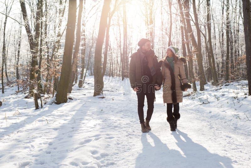Szczęśliwy pary odprowadzenie w lesie na śnieżnym wintertime obrazy royalty free