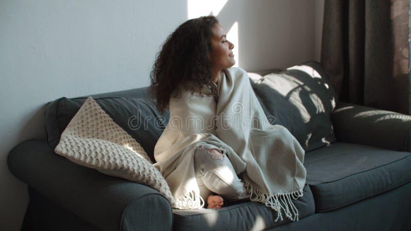 Szczęśliwy piękny kobiety obsiadanie na kanapie zawijającej w powszechny relaksować w domu zdjęcia royalty free