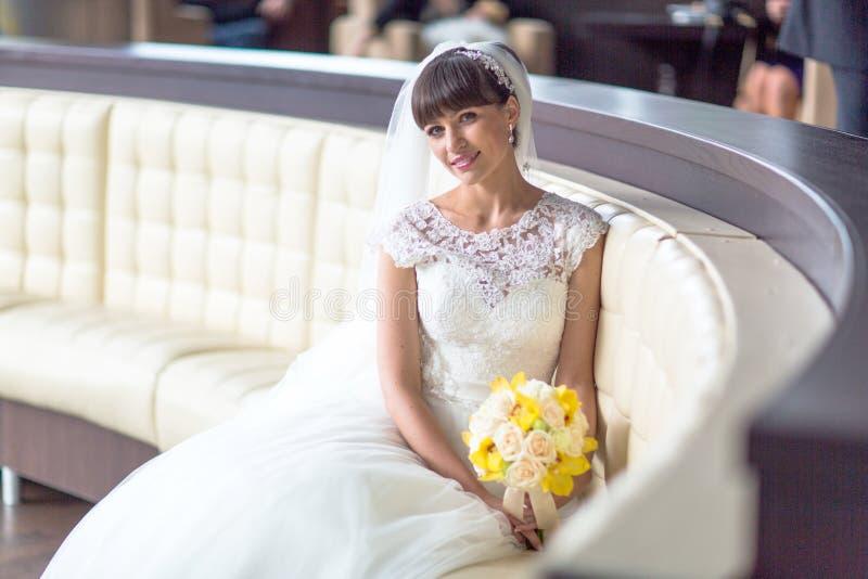 Szczęśliwy piękny panny młodej obsiadanie na eleganckiej białej kanapie obrazy stock