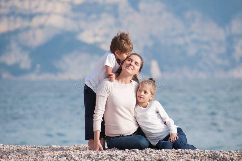 Szczęśliwy piękny rodzinny składać się z uśmiechnięty macierzysty i dwa dziecka całuje jej obsiadanie na morze plaży w chłodno la obraz stock