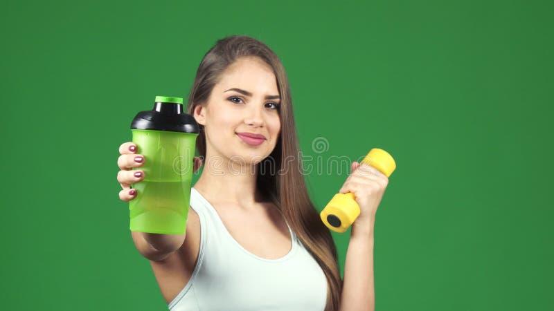 Szczęśliwy piękny sportsmenki mienia dumbbell i butelka wodny ono uśmiecha się obraz stock