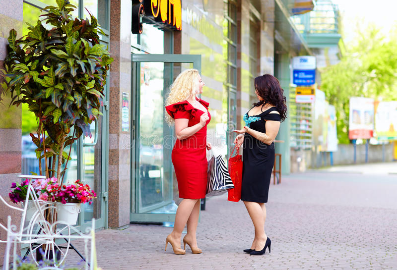 Szczęśliwy plus wielkościowe kobiety robi zakupy, opowiadający na ulicie obraz royalty free