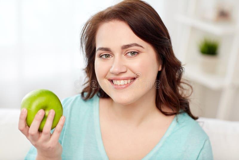 Szczęśliwy plus wielkościowy kobiety łasowania zieleni jabłko w domu zdjęcia stock