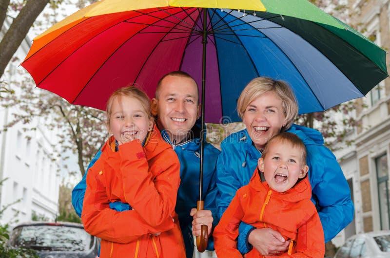 Szczęśliwy podeszczowy rodzinny uśmiech pod parasolem obrazy stock