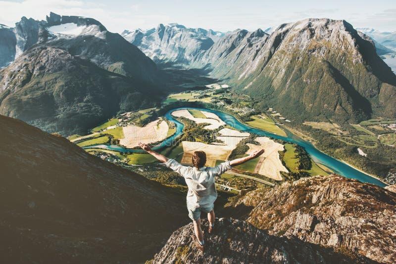 Szczęśliwy podróżnika mężczyzna podnoszący zbroi pozycję na falezie nad górami obraz royalty free