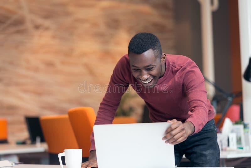 Szczęśliwy pomyślny amerykanina afrykańskiego pochodzenia biznesmen w nowożytnym początkowym biurze indoors zdjęcie royalty free