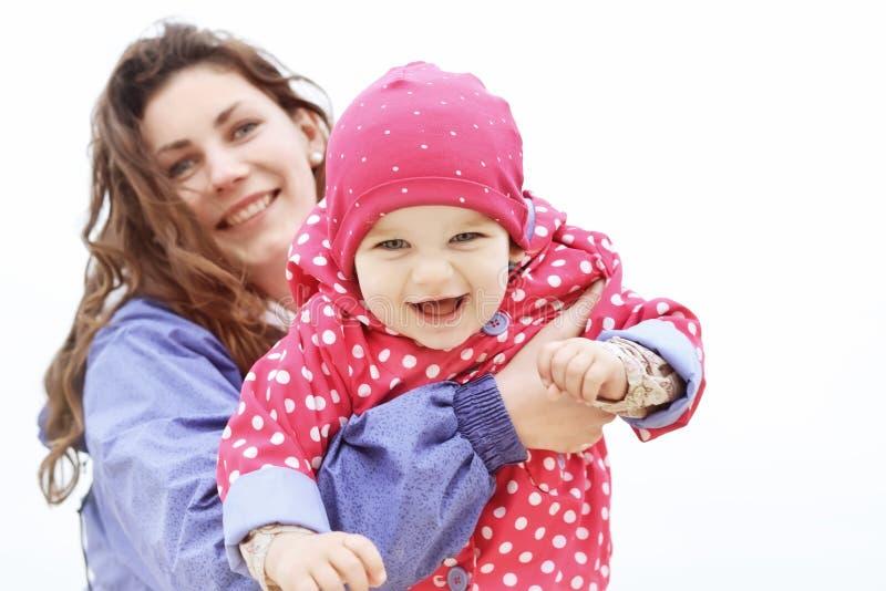 szczęśliwy portret rodzinny Śmiać się twarze, matkuje trzymać uroczej dziecko dziewczynki ono uśmiecha się i ściska Mama outdoors obrazy royalty free