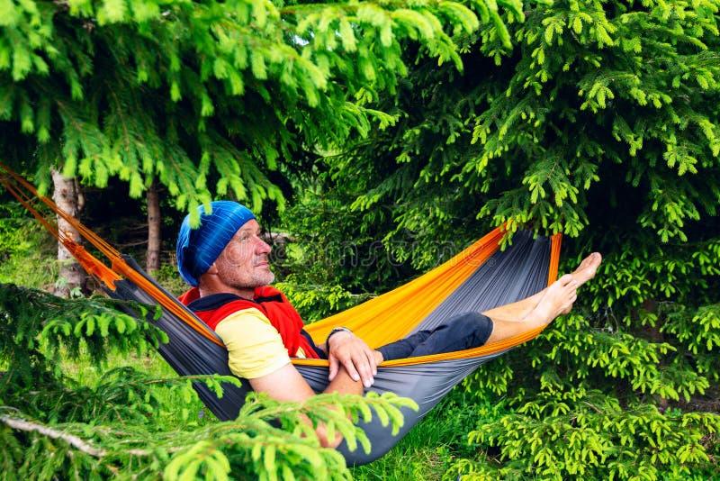 Szczęśliwy poszukiwacz przygód relaksuje w hamaku obrazy stock